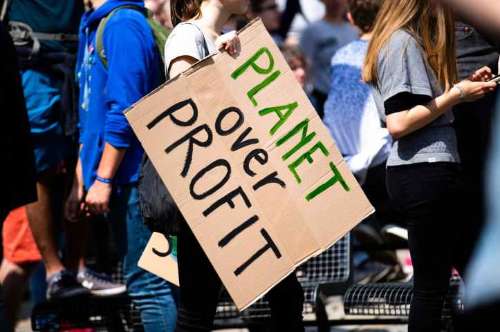 women holding a planet over profit sign